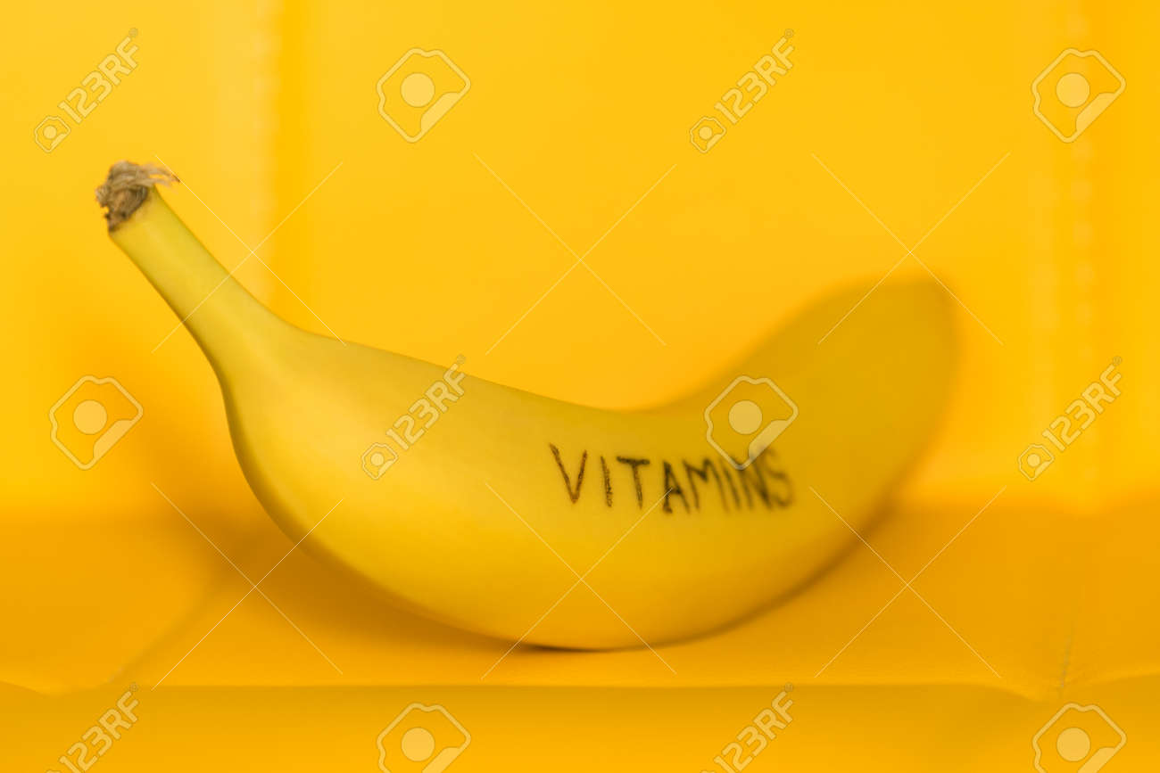 One fresh ripe banana fruit with text vitamins on yellow background - 170079227