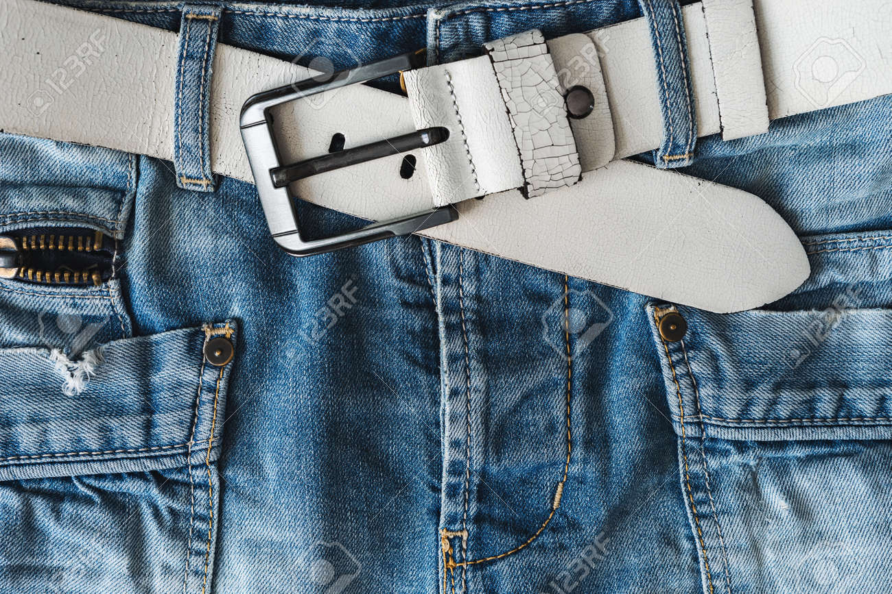 Blue casual jeans with white belt and pockets. Detail flat lay close-up view from above. Textured natural background - 171476120