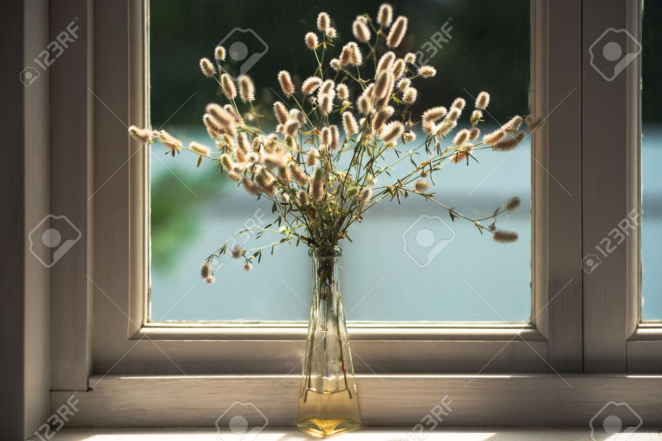 Dried field grass decoration in a vase on the windowsill in a rural house. Vintage faded colors - 172751673