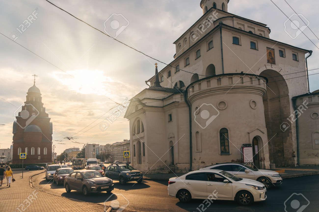 Vladimir, Russia - August 18, 2021: Transport moving on street near Golden Gate architecture landmark in sunny summer evening - 173498343