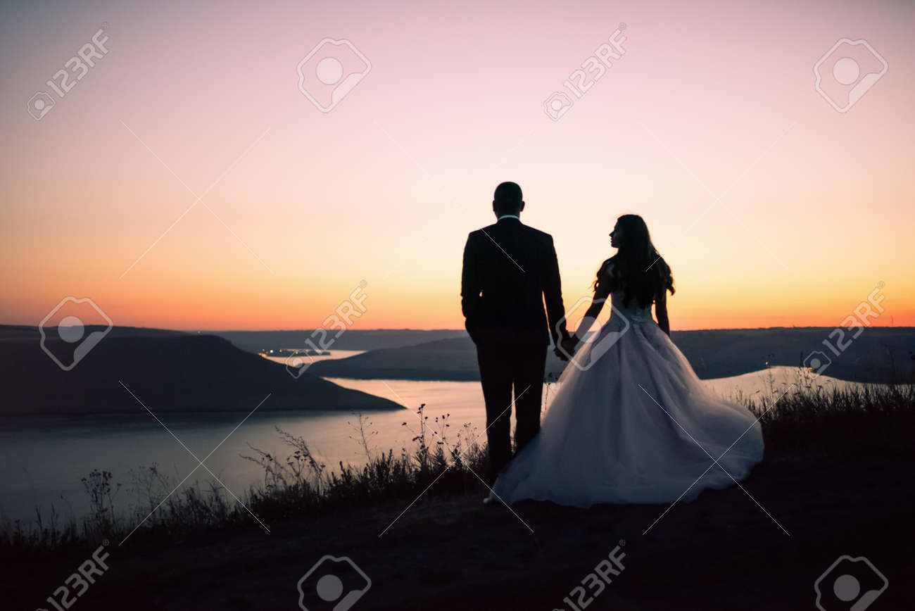 Silhouettes of bride and groom in wedding dress at night against backdrop of large lake and islands. Bakota, Ukraine - 158075173
