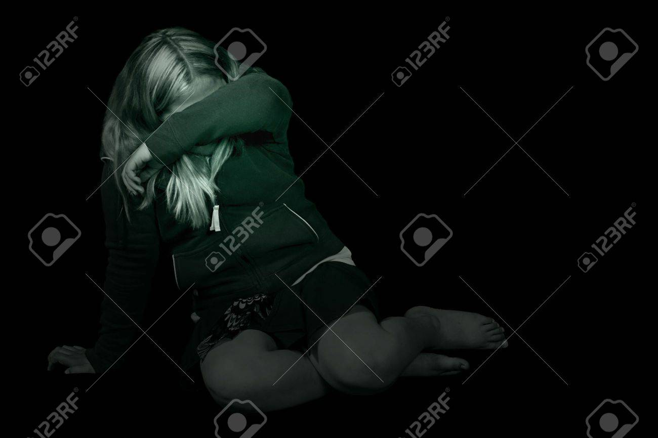 Black and white image of a young girl cowering in a dark room, hiding from the abuse Stock Photo - 5022817