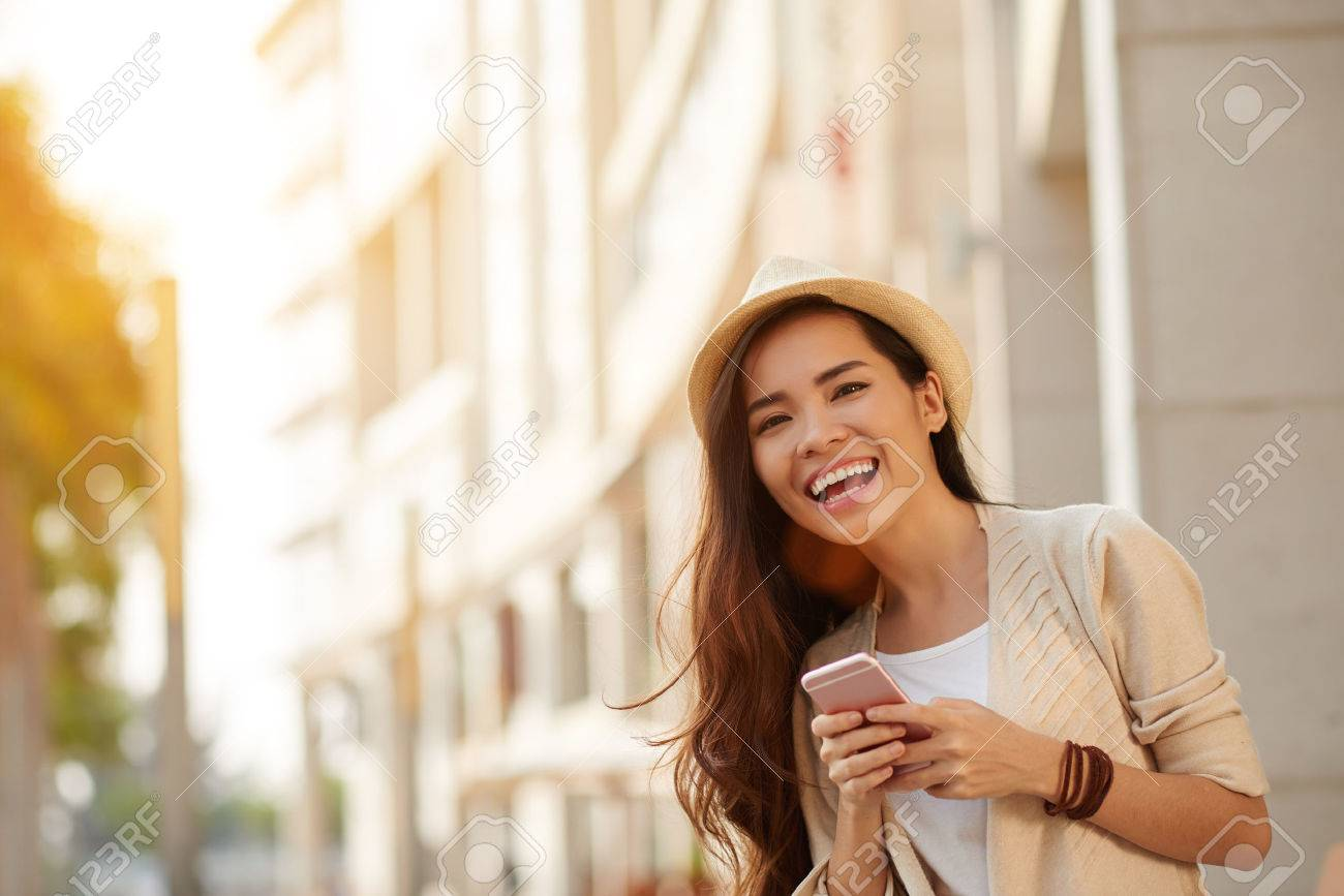 Happy young Asian woman with smartphone standing in the street - 66125404