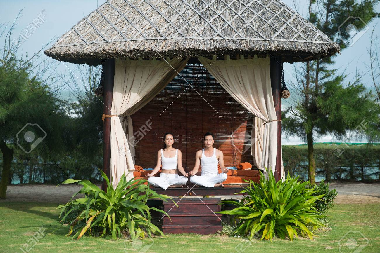 Man And Woman Practicing Yoga In Hut Stock Photo Picture And