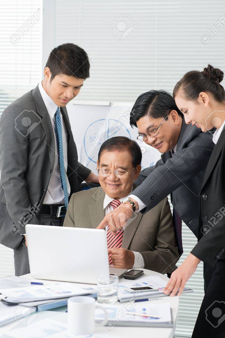 office meeting. Stock Photo - Vertical Shot Of A Business Team Discussing At The Meeting Office