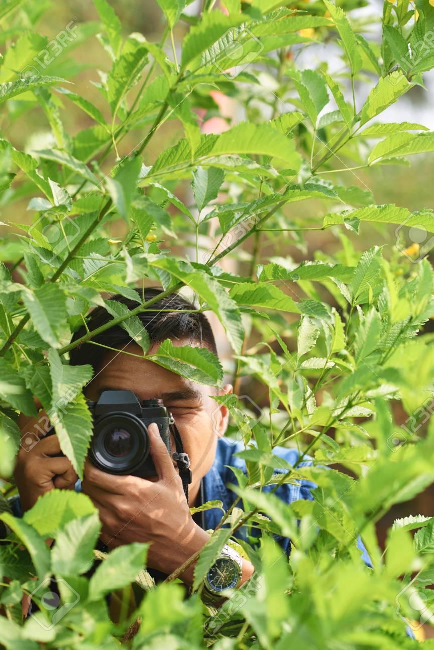 77171950-man-with-digital-camera-hiding-