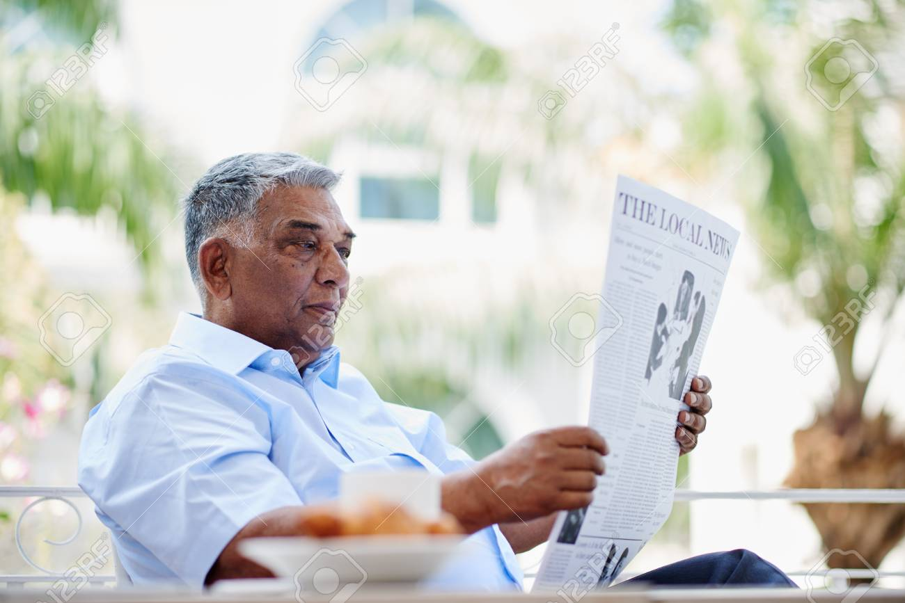 senior indian man reading newspaper in the morning stock photo