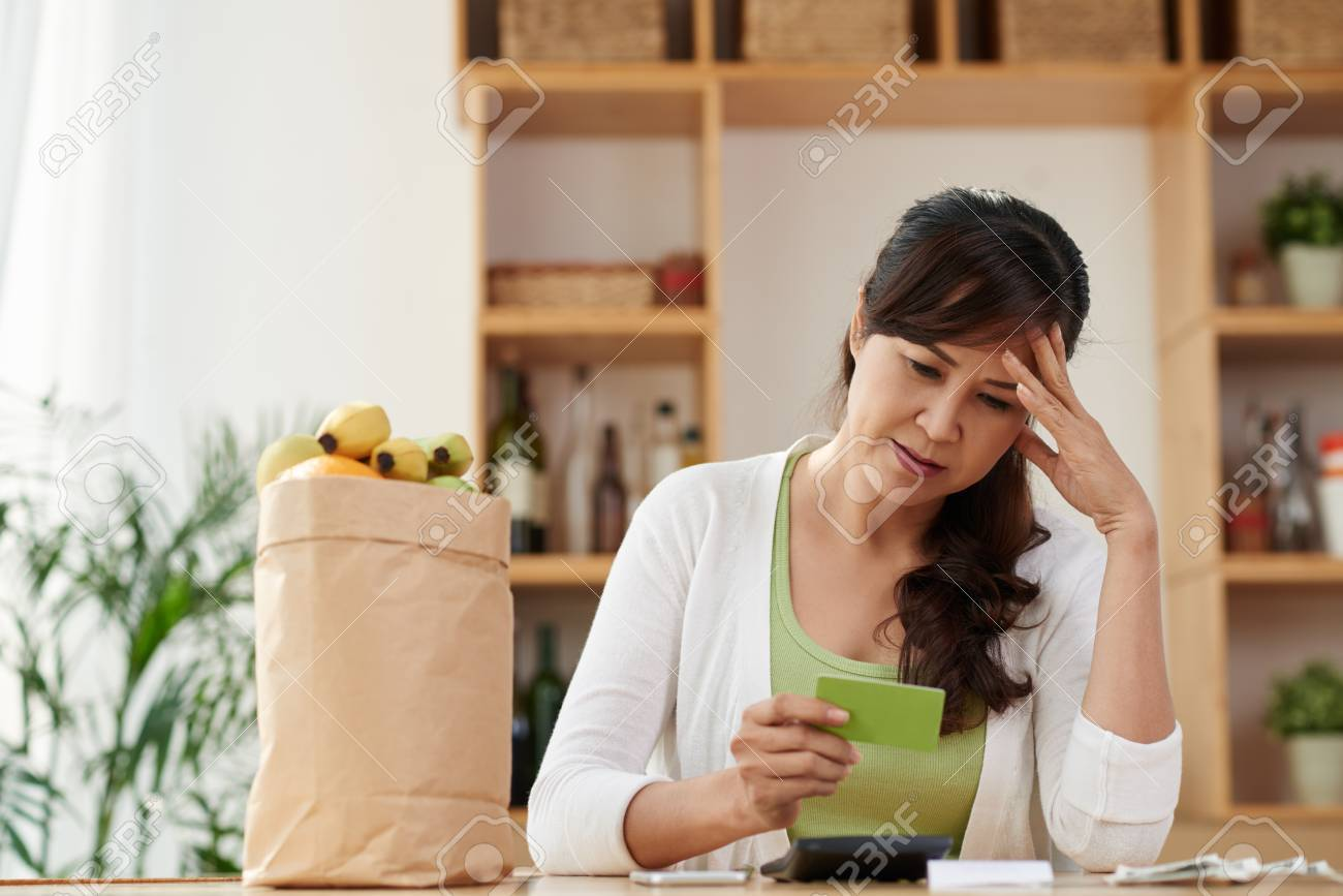 unhappy mature housewife looking at credit card after shopping stock