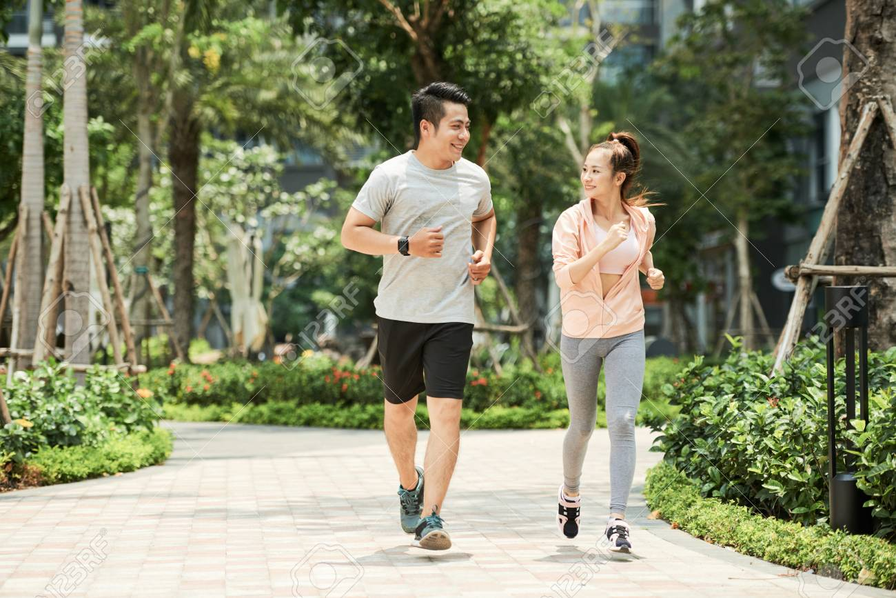 Vietnamese man and woman jogging together in the park - 102256731