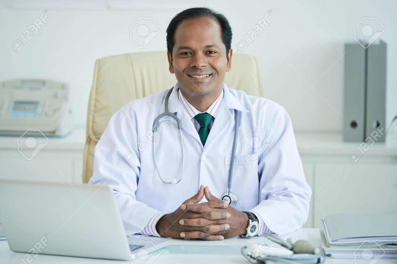 Portrait of smiling Indian male doctor sitting at his workplace - 103366692