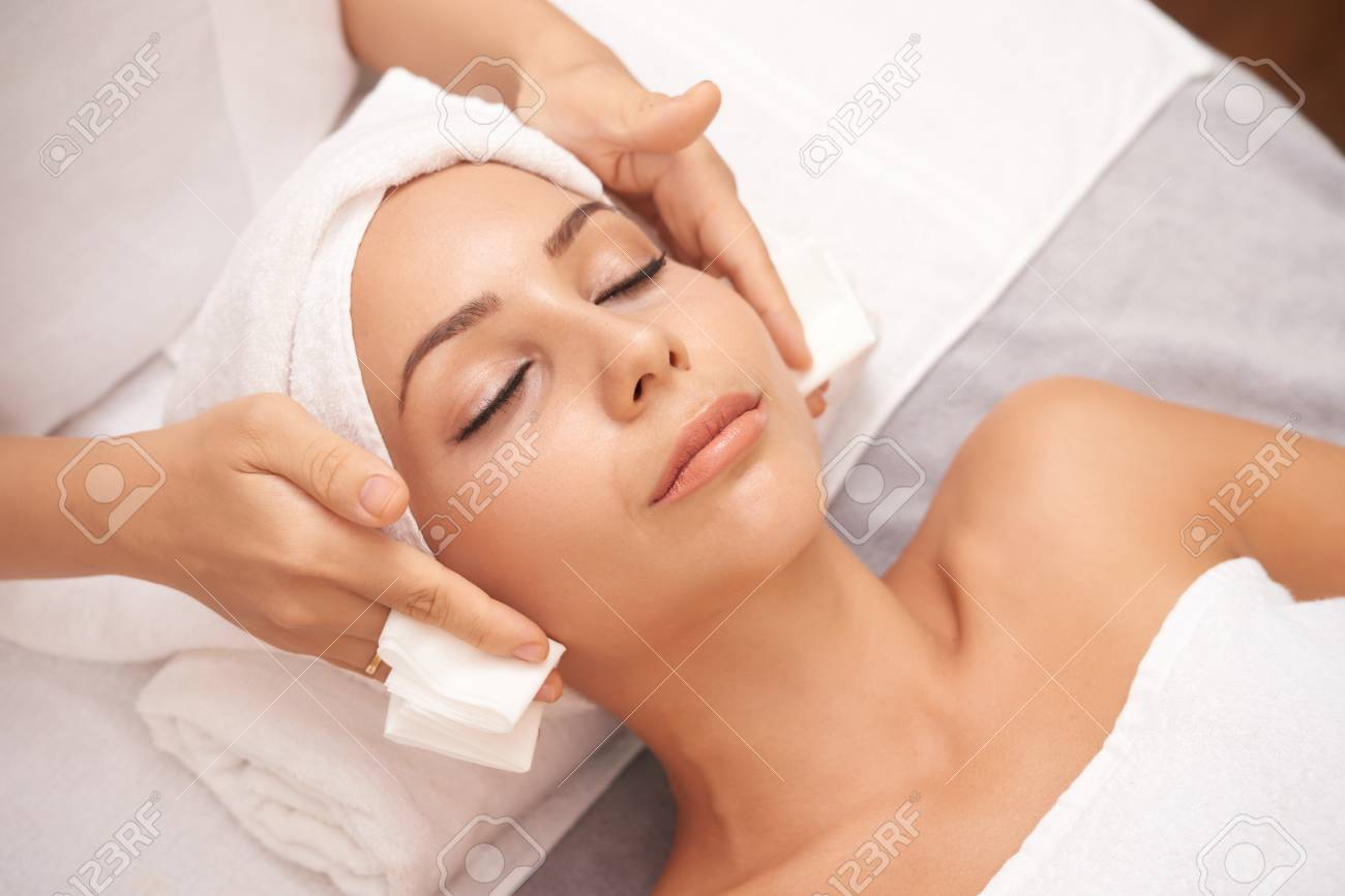 Beautiful young woman with flawless skin enjoying professional facial in beauty salon - 106088072