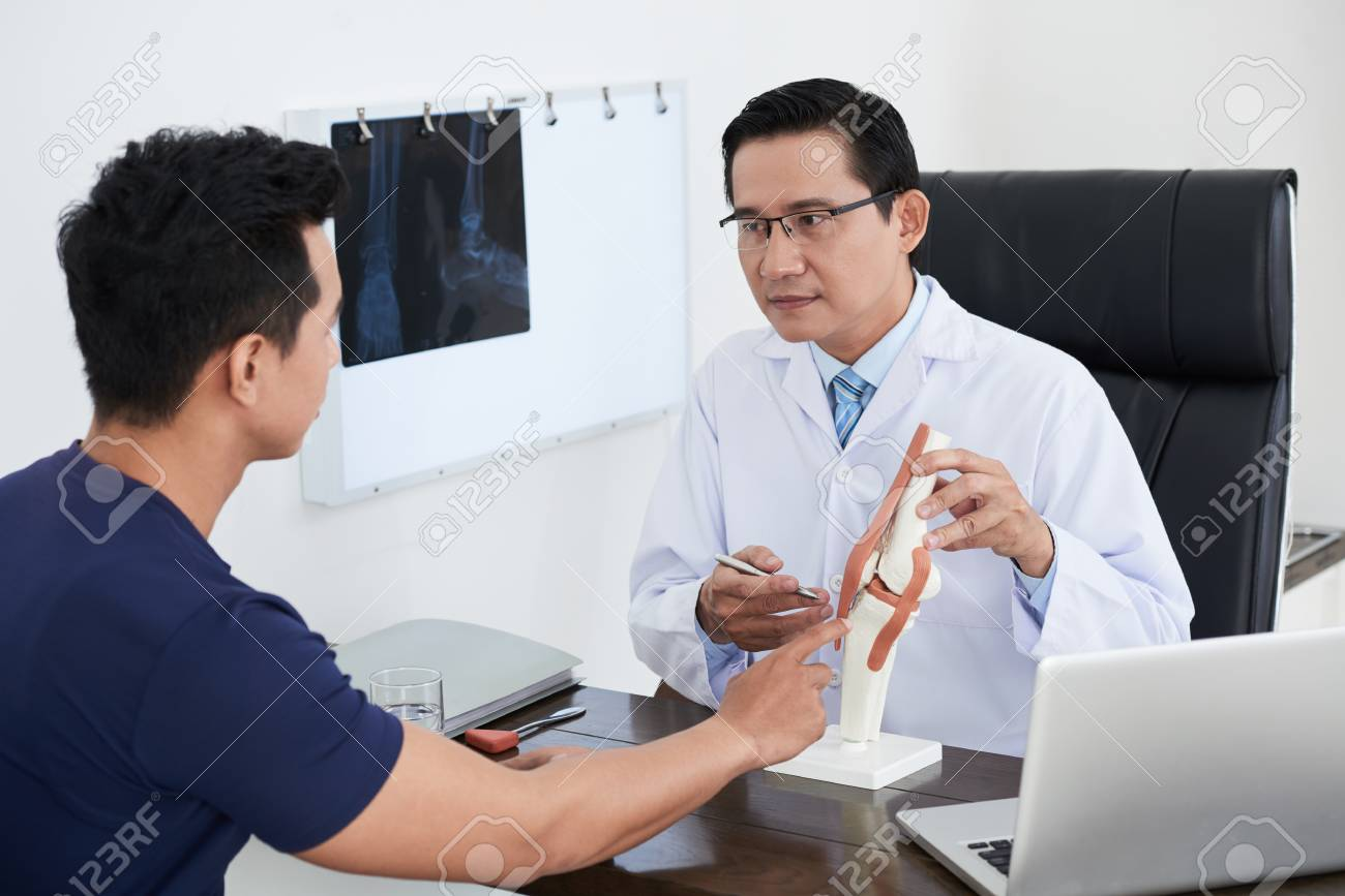 Doctor explaining structure of joint to patient - 106581333
