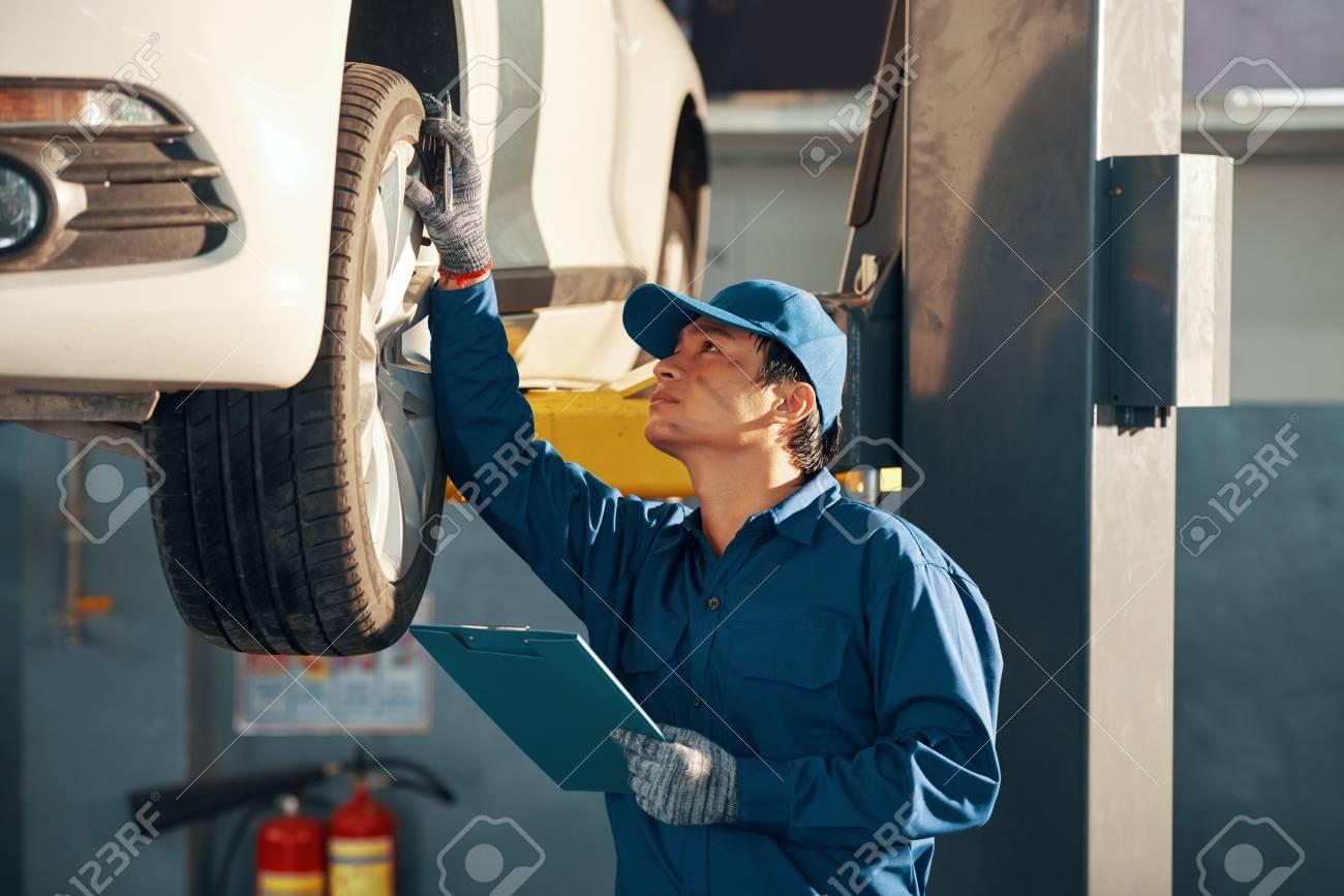 Mechanic checking car - 107064706