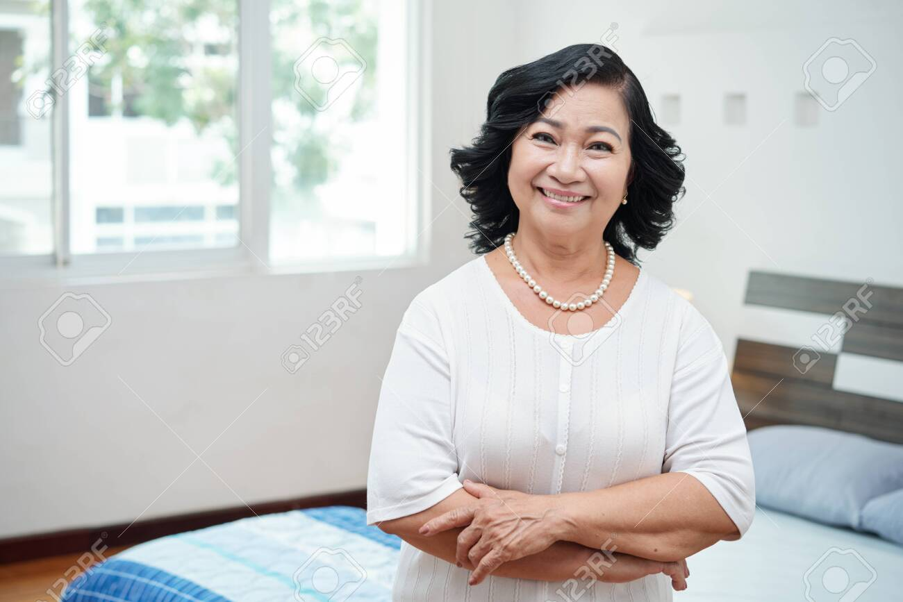 Waist-up portrait of attractive retired Asian woman with pearl necklace standing in bedroom with crossed hands and smiling at camera - 109222868