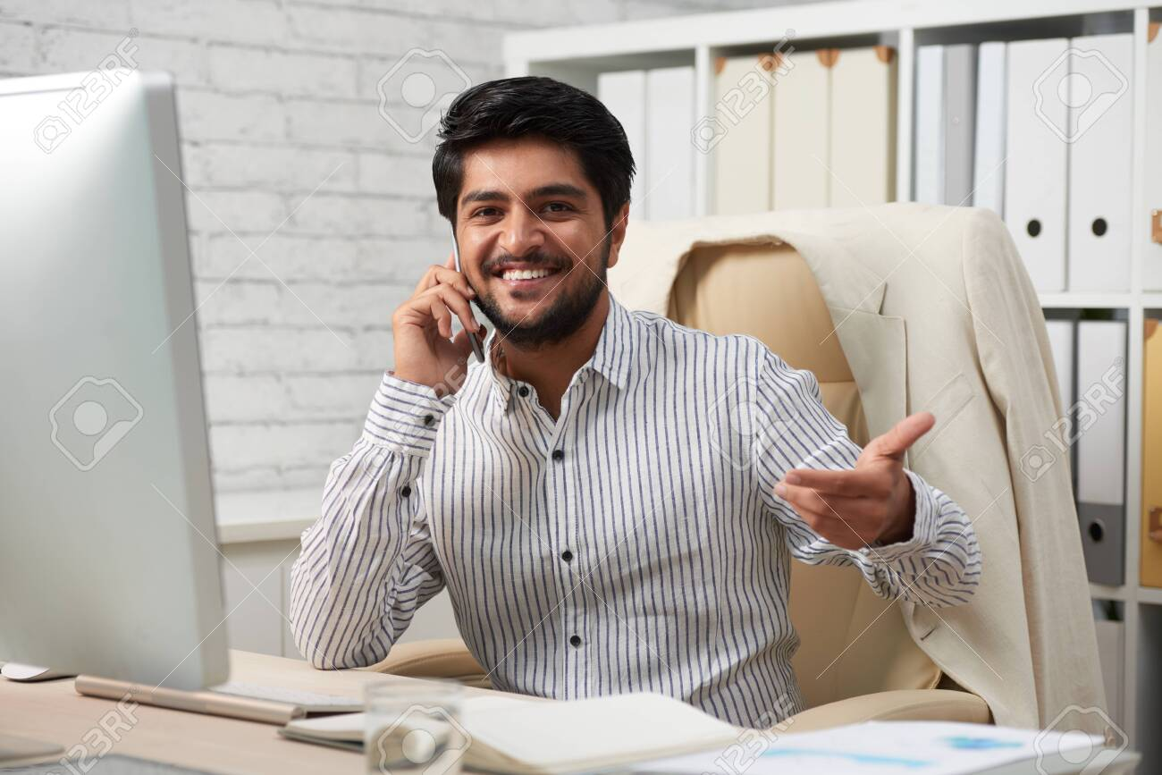 Portrait of smiling Indian businessman with smartphone - 118147556