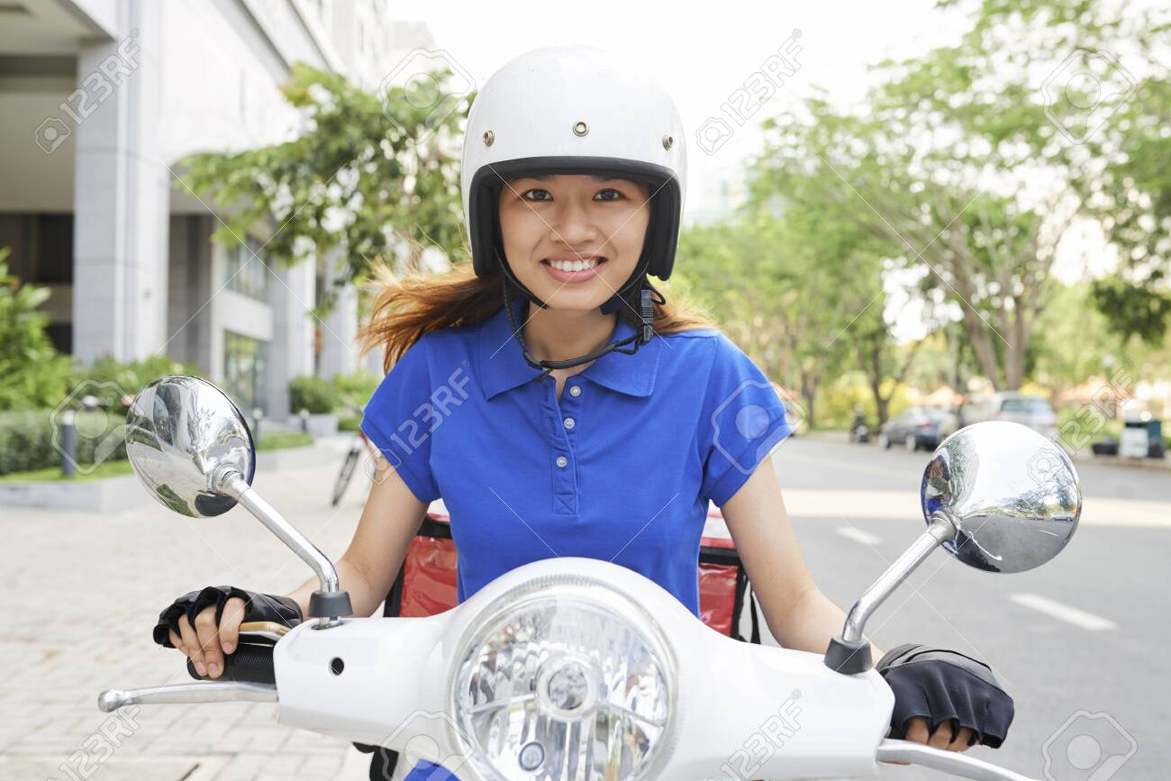 Portrait of female happy food courier on scooter in hurry to deliver lunch - 122708249