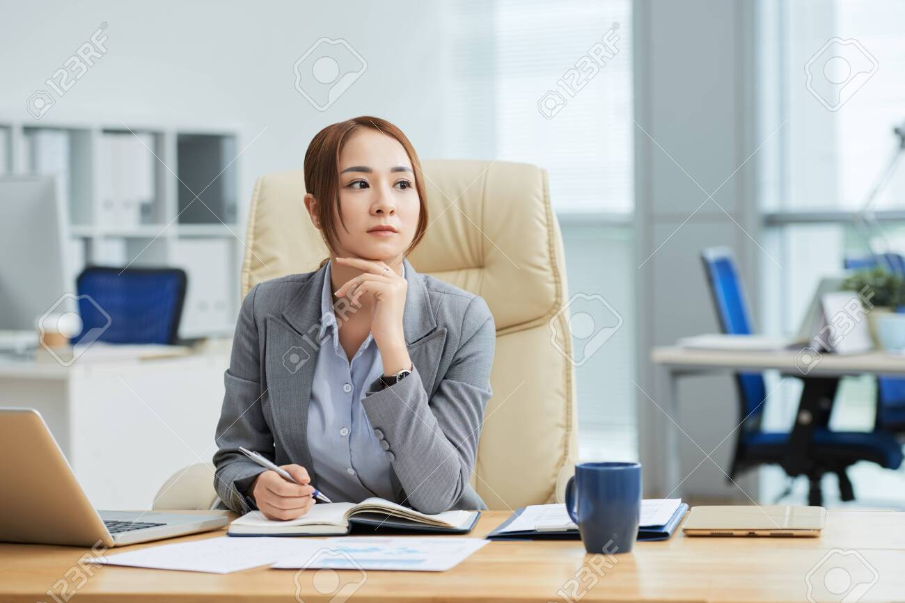 Serious Asian businesswoman sitting at her workplace with notepad and thinking over new business ideas at office - 123324598