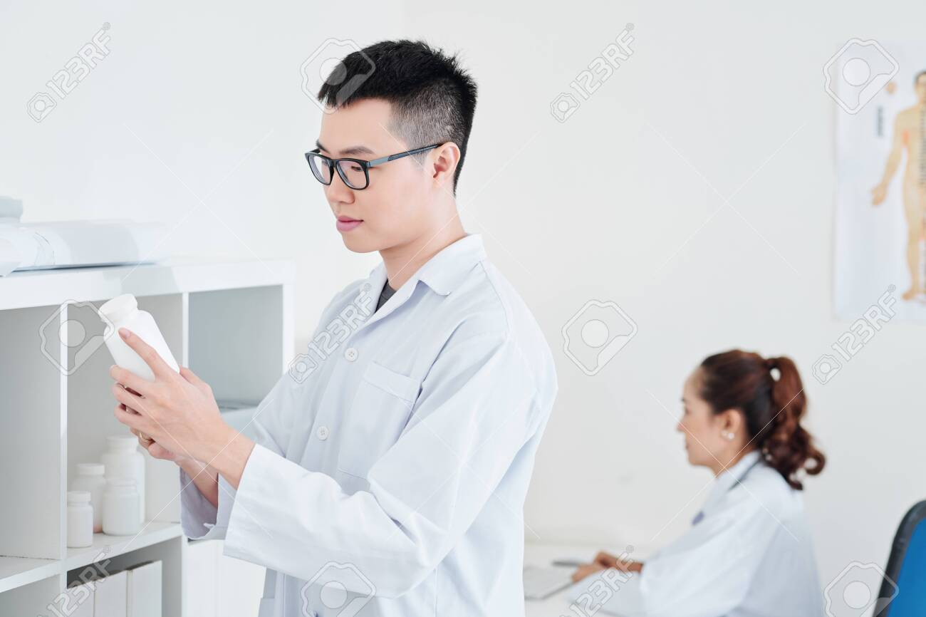 Young Vietnamese doctor reading contraindications on container with tablets and pills - 128303537
