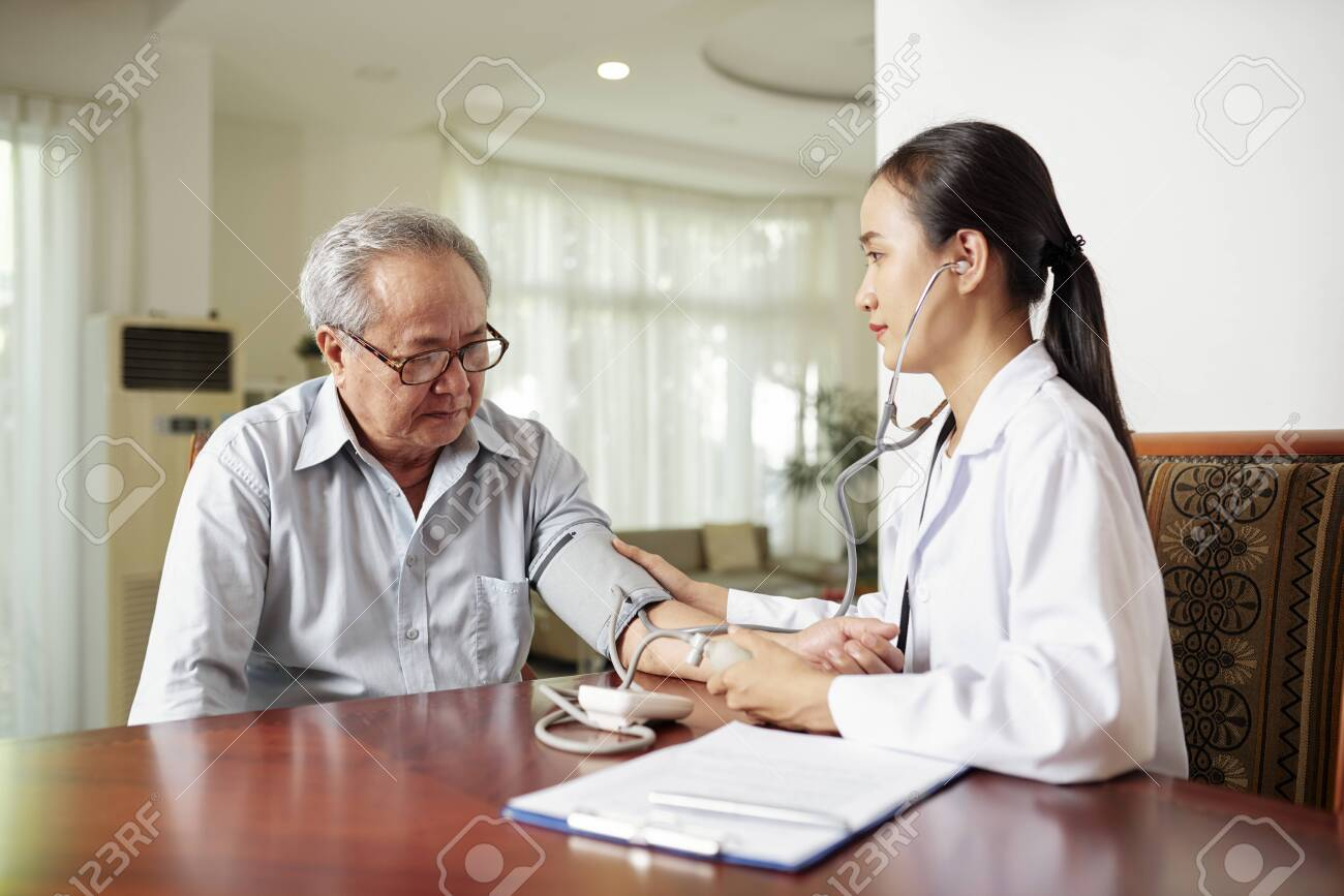 Asian young nurse sitting at the table together with elderly man and examining his blood pressure during her visit at home - 127818908