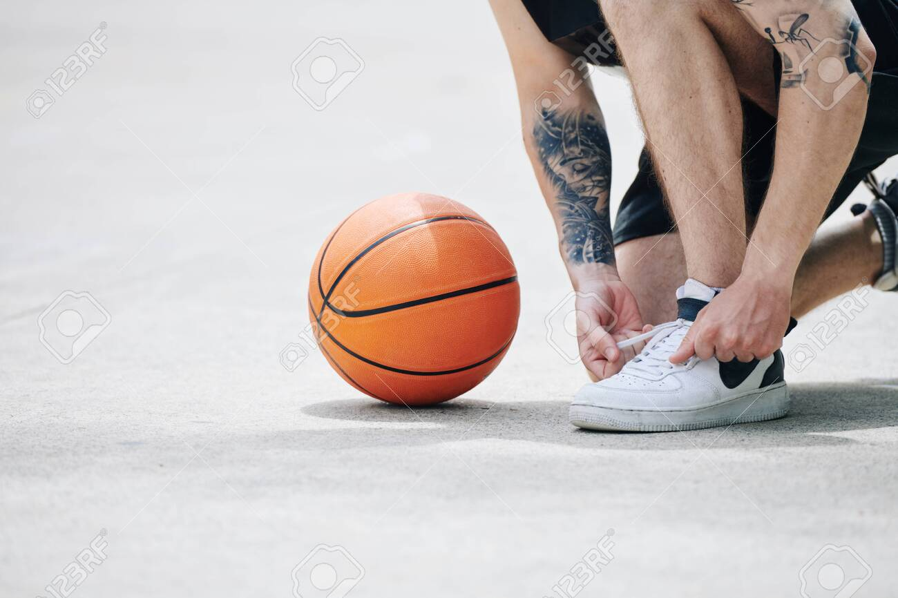 Basketball Player Tying Sports Shoes