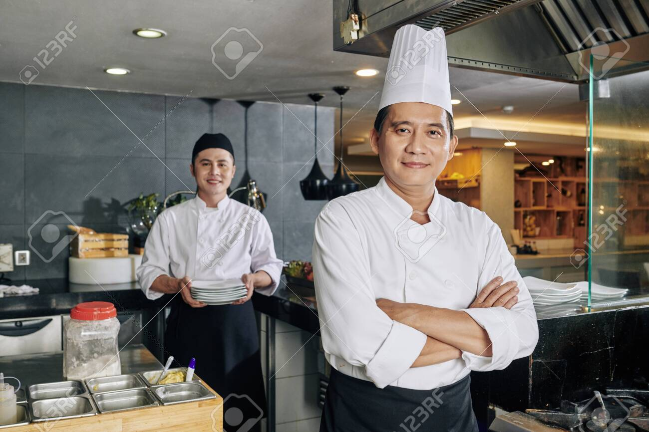 Portrait of confident Asian chef standing with arms crossed and looking at camera with young cook preparing food in the background in the kitchen - 130125469
