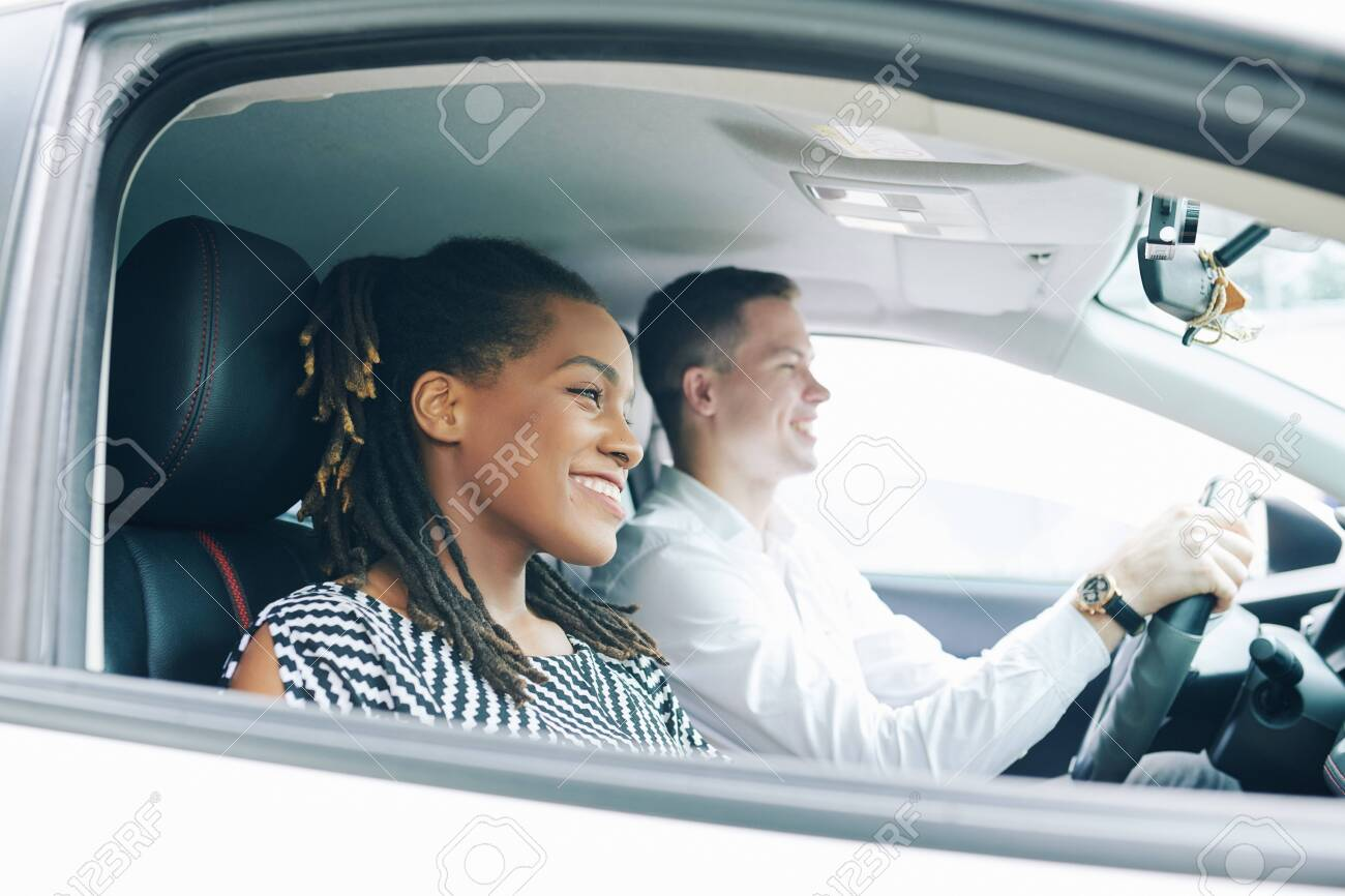 Happy African woman sitting near the young man who driving a car they driving and smiling - 130125442