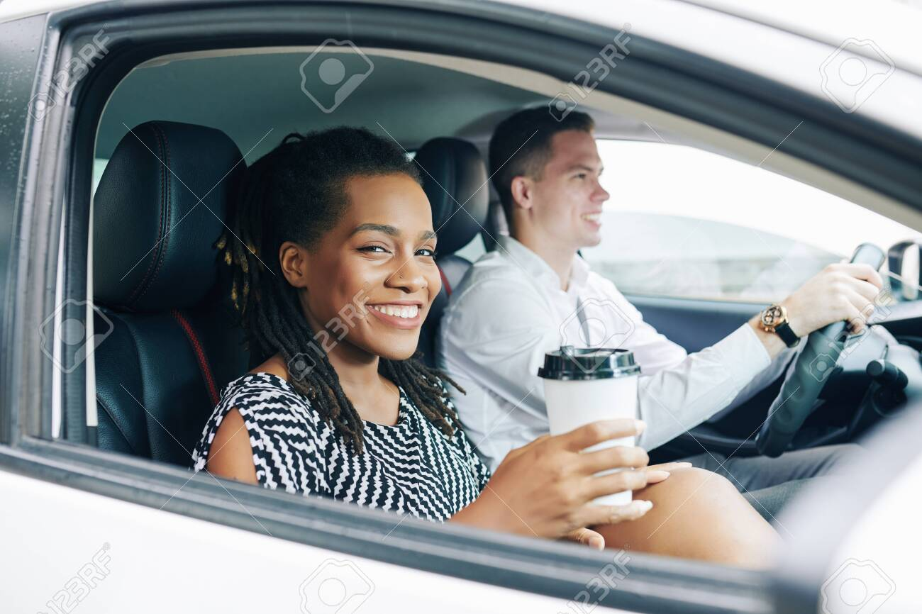 African young woman smiling at camera while drinking coffee during her trip by car together with young man - 130125349