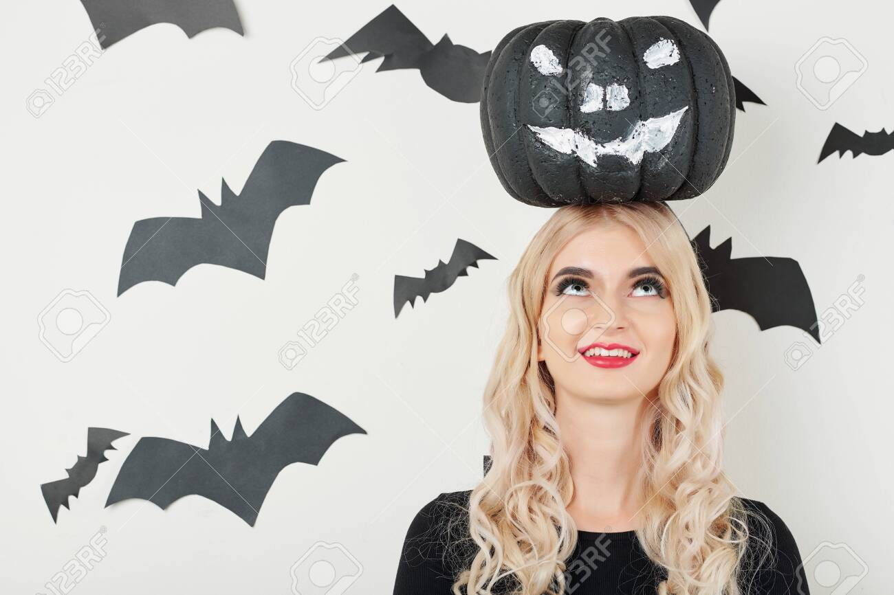 Cheerful young woman smiling and looking up at black painted pumpkin on her head - 131067259