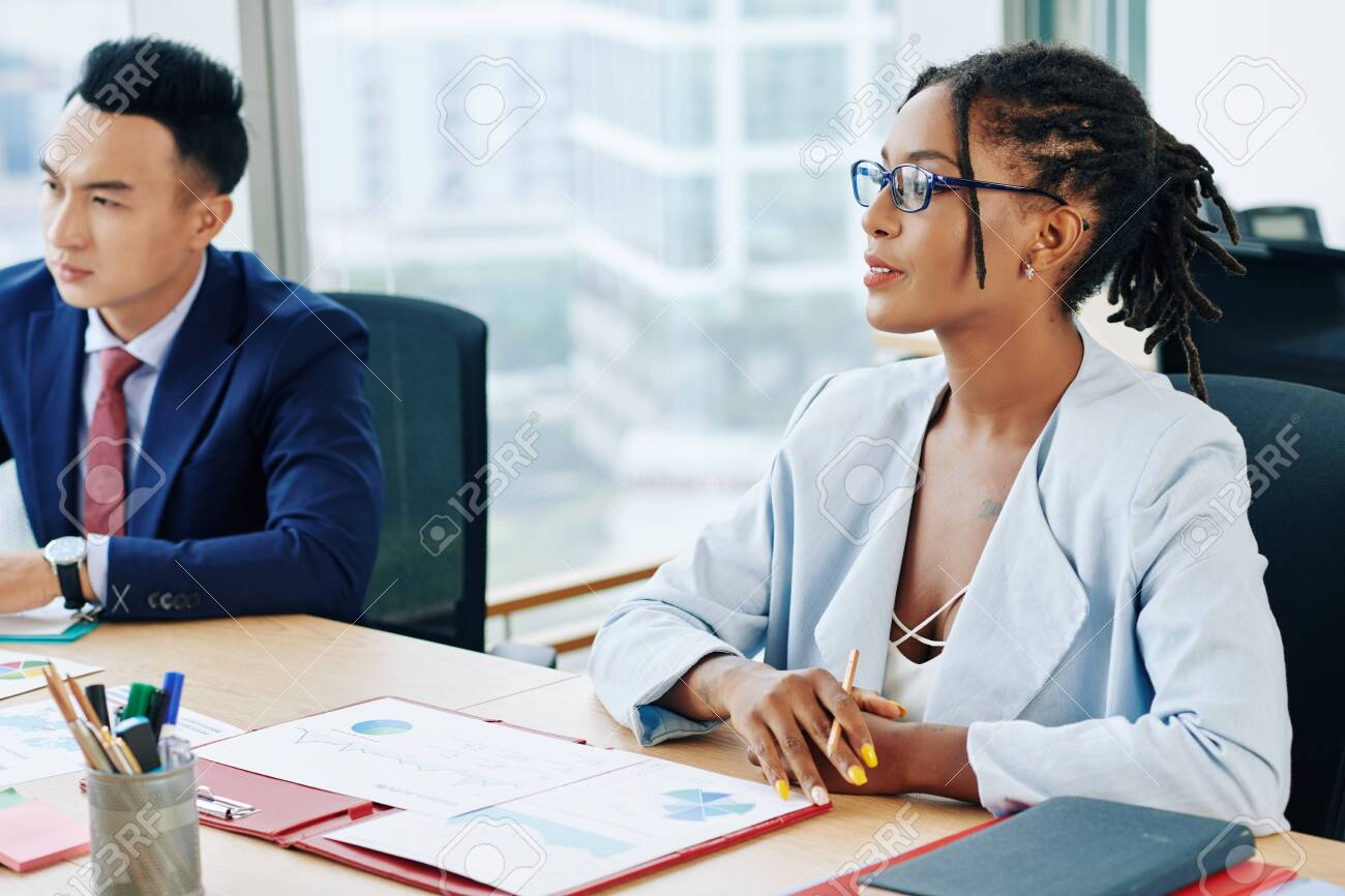 Pretty businesswoman with dreadlocks sitting at big table with coworkers and discussing financial documents at meeting - 135450465