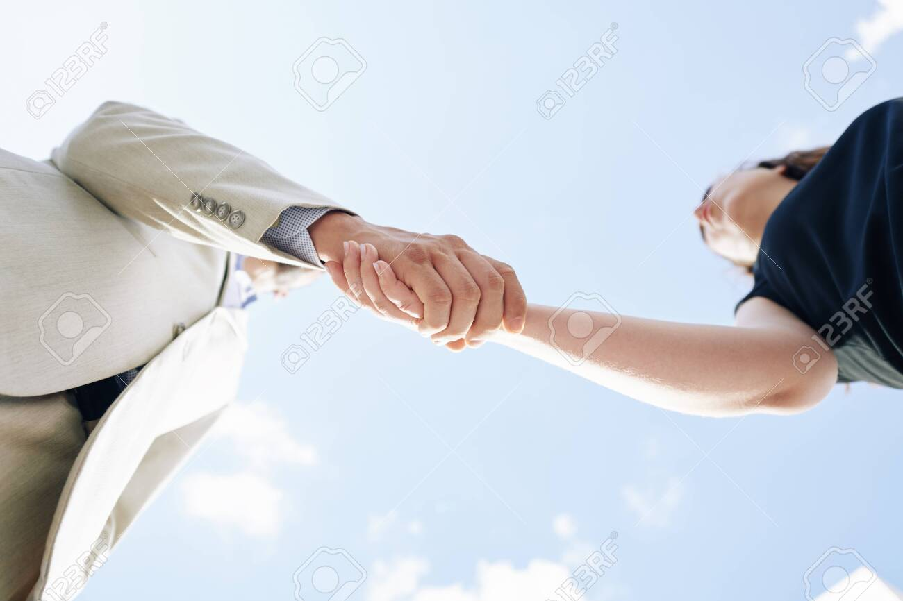 Business partners shaking hands and greeting each other, view from below - 155196571