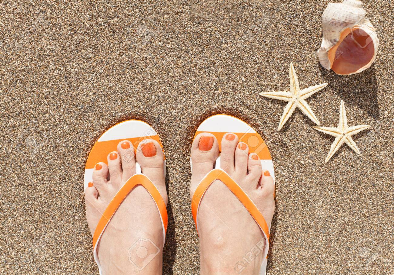 674776f560924 Stock Photo - Woman feet wearing flip flops on a beach