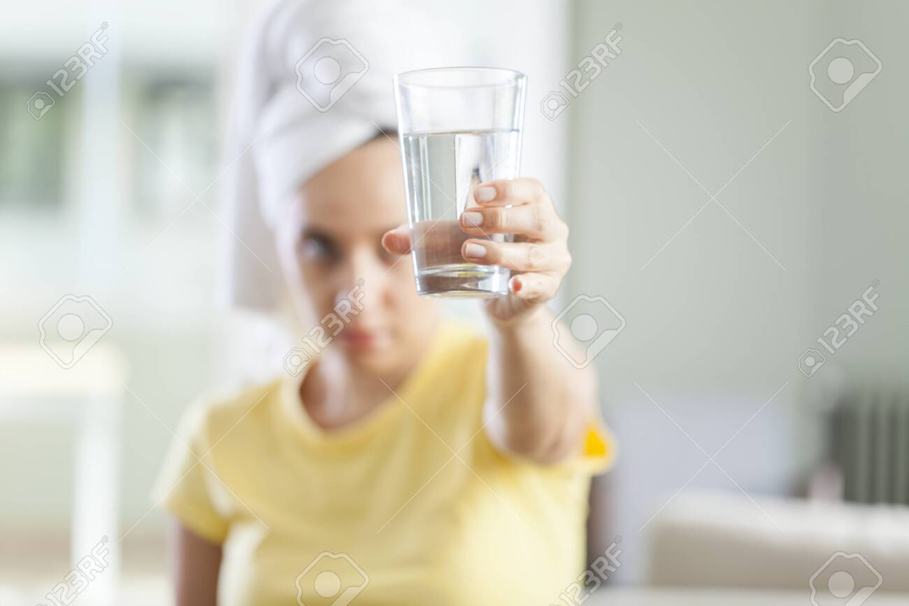 Young woman holds a glass with water on living room - 134469384