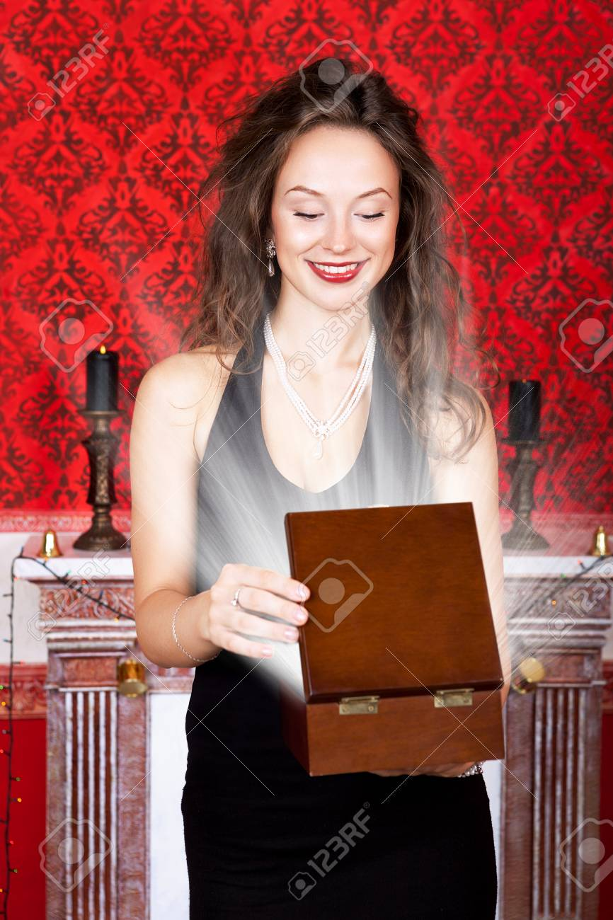 Beautiful woman smiling and opening a wooden gift box with rays in red vintage interior. Merry Christmas and Happy New Year theme. Retro and rich interior Stock Photo - 23781100