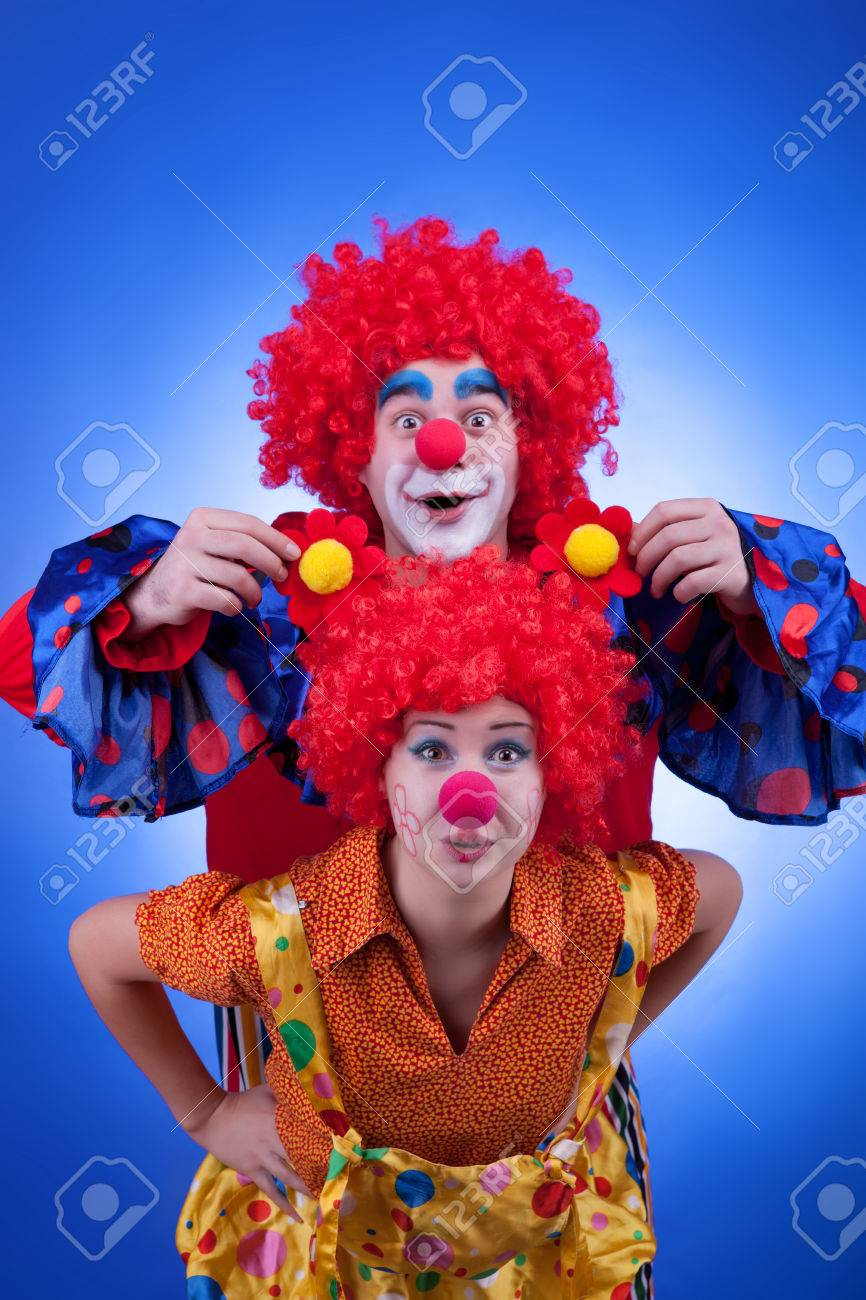 two happy clowns playing on blue background professional studio