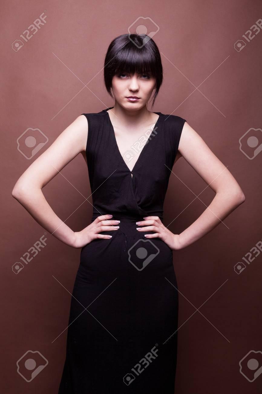6b88a20f3bcd Archivio Fotografico - Bello modello in vestito nero lungo su priorità  bassa marrone in foto dello studio. Bellezza e moda Modello di prova