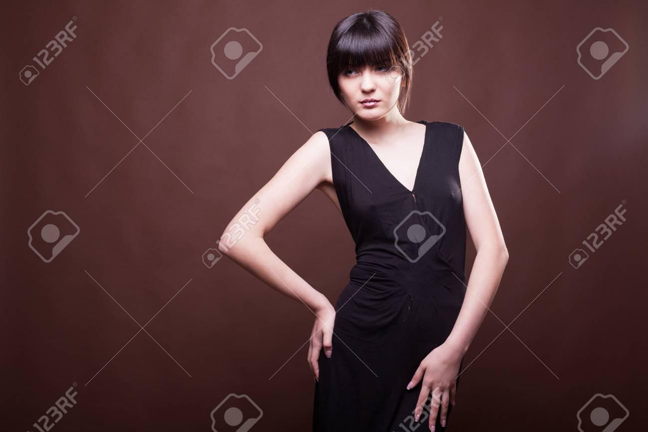 370669f2c2 Donna attraente in vestito nero lungo su priorità bassa marrone in foto  dello studio. Bellezza e moda Modello di prova