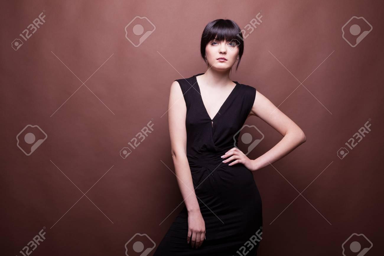 3f5a96e7c6b5 Archivio Fotografico - Splendida donna in abito lungo nero su sfondo  marrone in studio fotografico fotografico e bellezza. modello di prova