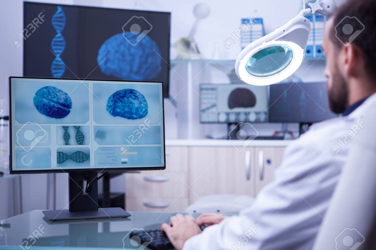 Young medical assistant working on computer in a hospital laboratory. Brain diagnosis. - 128645985