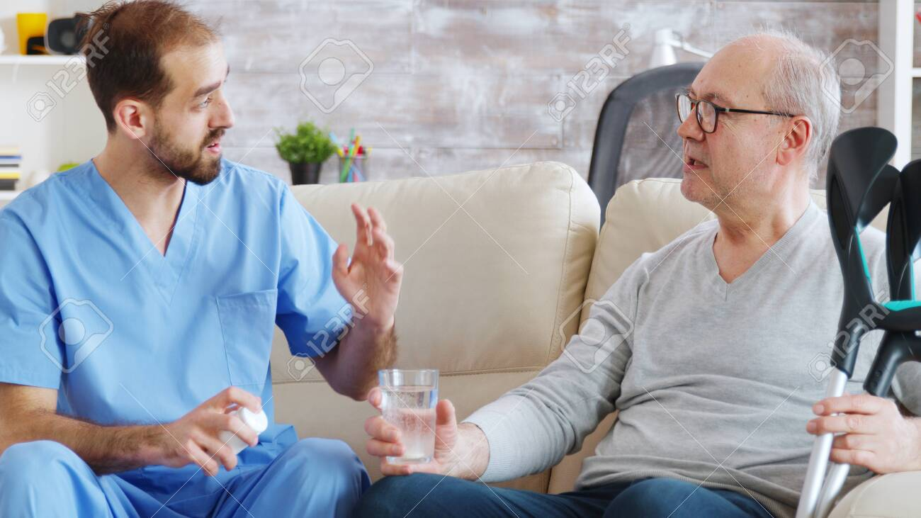 Male nurse giving pills to retired man in nursing home. - 141670669