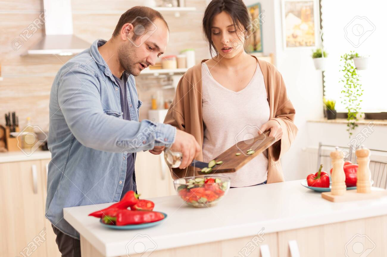 Man pouring olive oil on salad in kitchen. Healthy salad with fresh vegetables. - 152804780