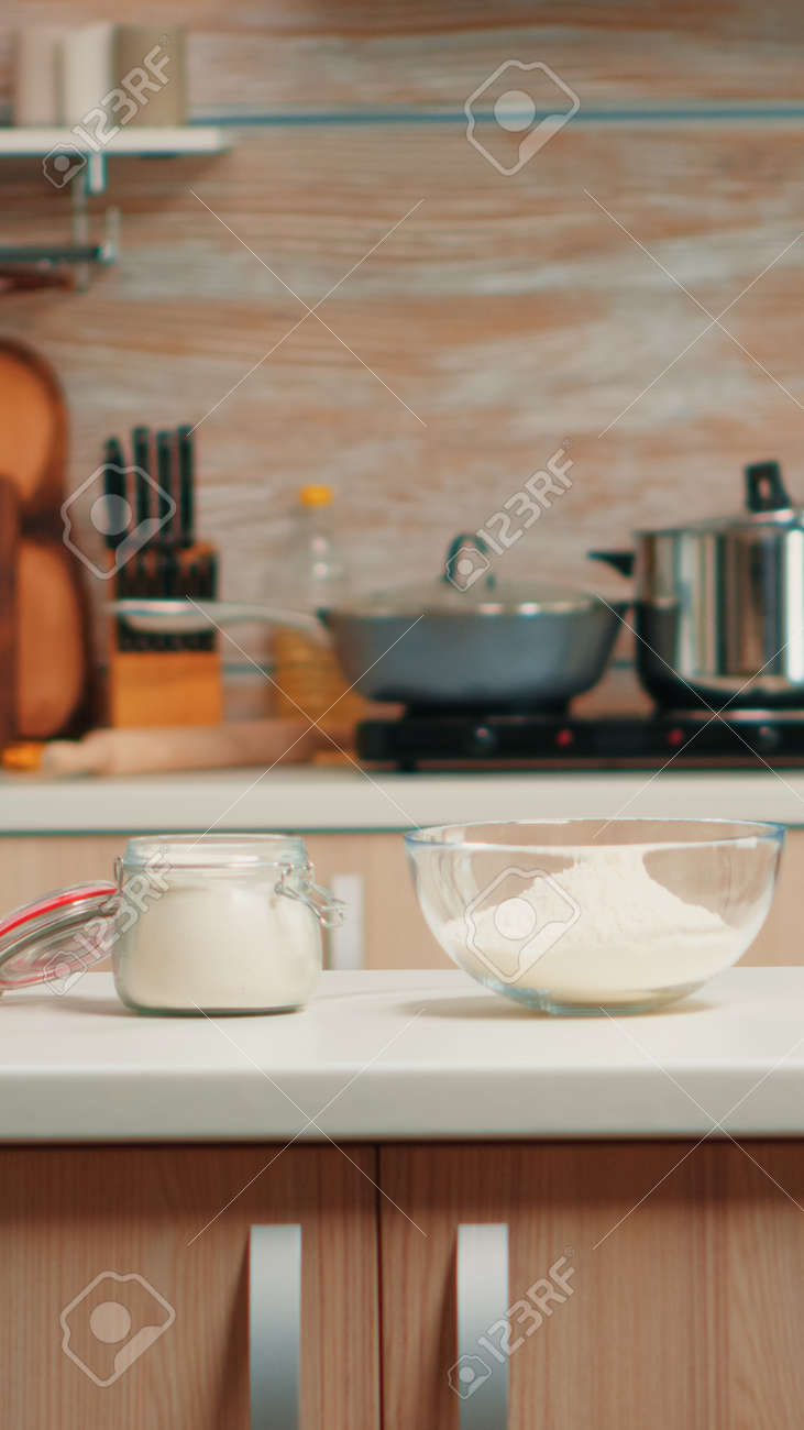 Pastry ingredients for homemade cakes and bread in empty kitchen. Modern dining room equipped with utensils ready for cooking with wheat flour in glass bowl and fresh eggs on table - 157769976