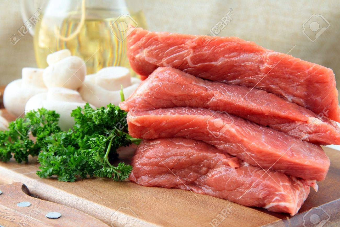 Fresh raw beef  with mushrooms and parsley  on wooden cutting board Stock Photo - 9034012