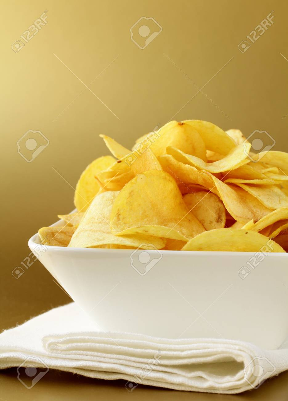 potato chips in a white bowl on a gold background Stock Photo - 12522836