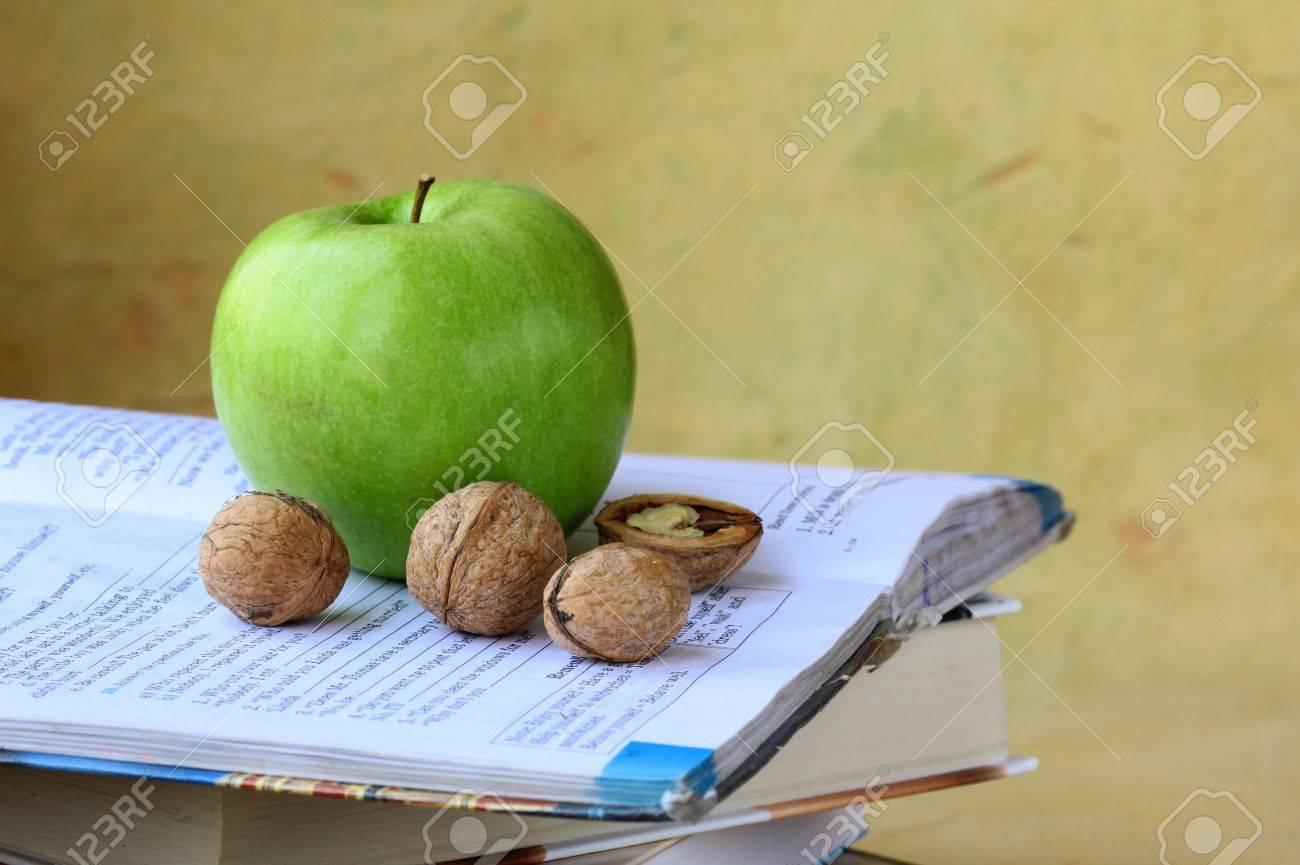 green apple and walnuts on a pile of books Stock Photo - 13540676