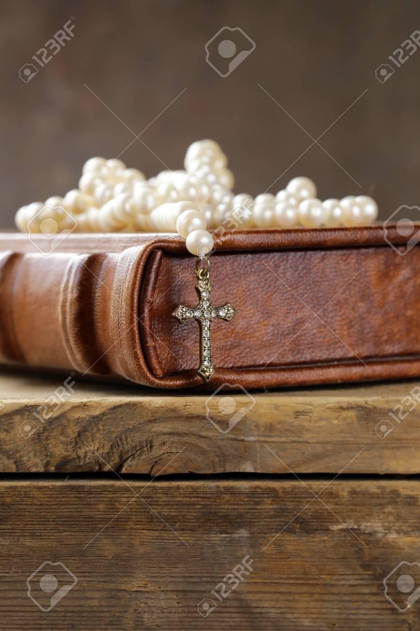 78b17701c039 Foto de archivo - Libro viejo (biblia) y el símbolo cristiano cruzan el  collar de perlas
