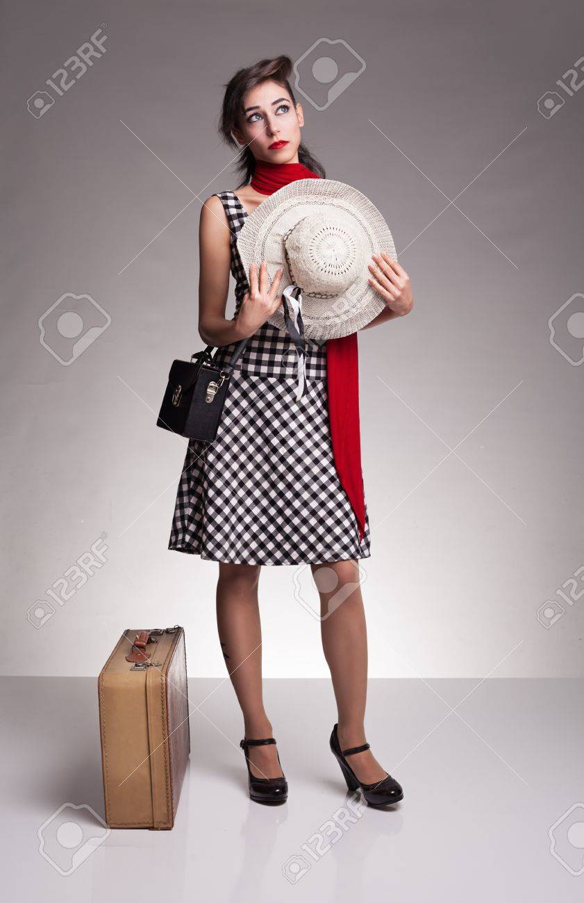 young sad woman with plaid strap dress, holding her hat and  waiting desperately on grey background Stock Photo - 18617051