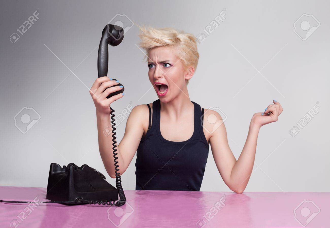 angry young lady shouting and holding handset in her hand Stock Photo - 18618154