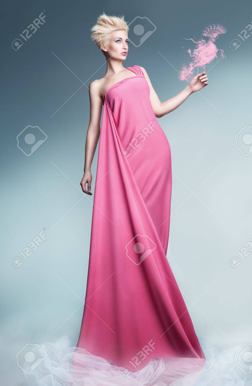 beautiful young model holding a peacock made of smoke wearing long pink dress and posin on blue background Stock Photo - 18618173