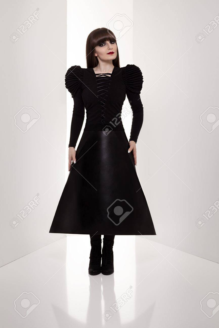 beautiful woman in black futuristic clothes standing and looking at camera between two gray walls on white background Stock Photo - 18952080