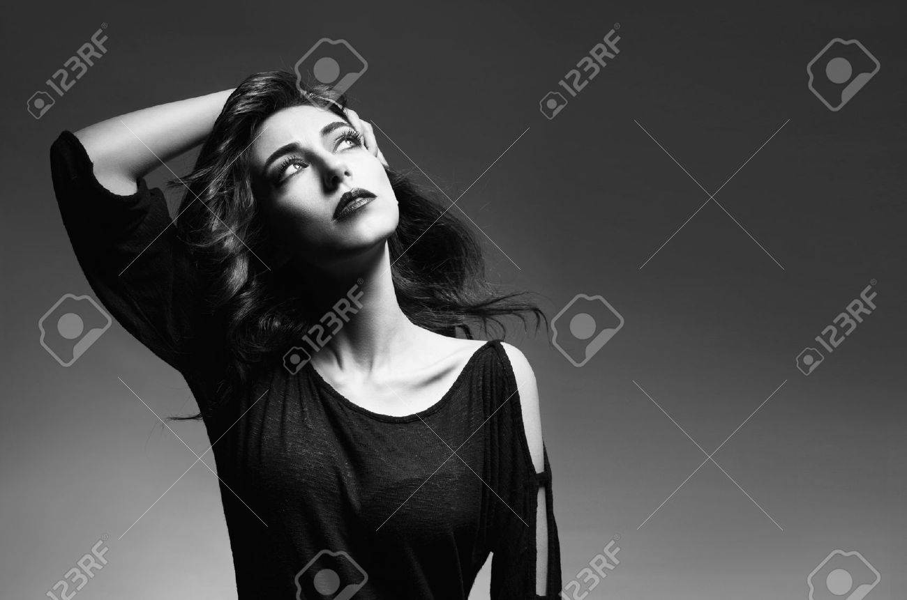 black and white image of beautiful brunette model touching her hair and looking up on grey background Stock Photo - 18952307